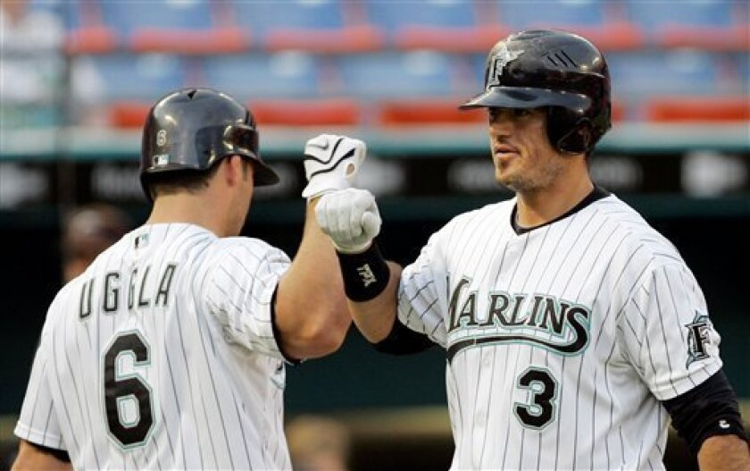 Florida Marlins' Jorge Cantu (3) is congratulated by teammate Dan Uggla (6) after Cantu hit a two-run home run against Milwaukee Brewers' Carlos Villanueva in the first inning of a baseball game in Miami, Thursday, May 8, 2008. Hanley Ramirez scored on the home run. (AP Photo/Alan Diaz)