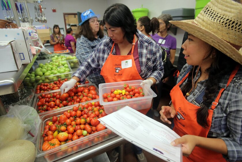 Nutrition service employees Hilda Culver (center) and Carmen Montiel (right) pick out fresh food to make a chicken salad Friday during a harvest festival at Oceanside High School.
