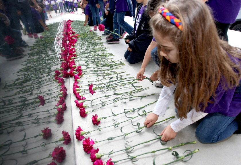 Chamlian Armenian School second-grade students lay carnations during the annual Armenian Genocide Commemorative Walk to the Armenian Western Prelacy Headquarters in La Crescenta on Thursday, April 7, 2016. At the headquarters, the students laid down carnations at an Armenian Genocide Memorial.