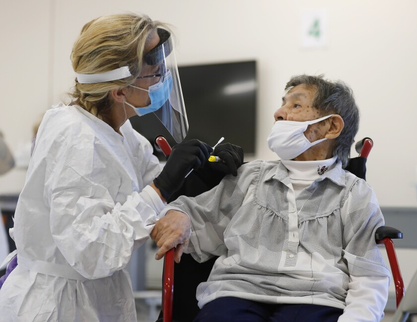 A nurse administers a coronavirus test for Esperanza Gomez.