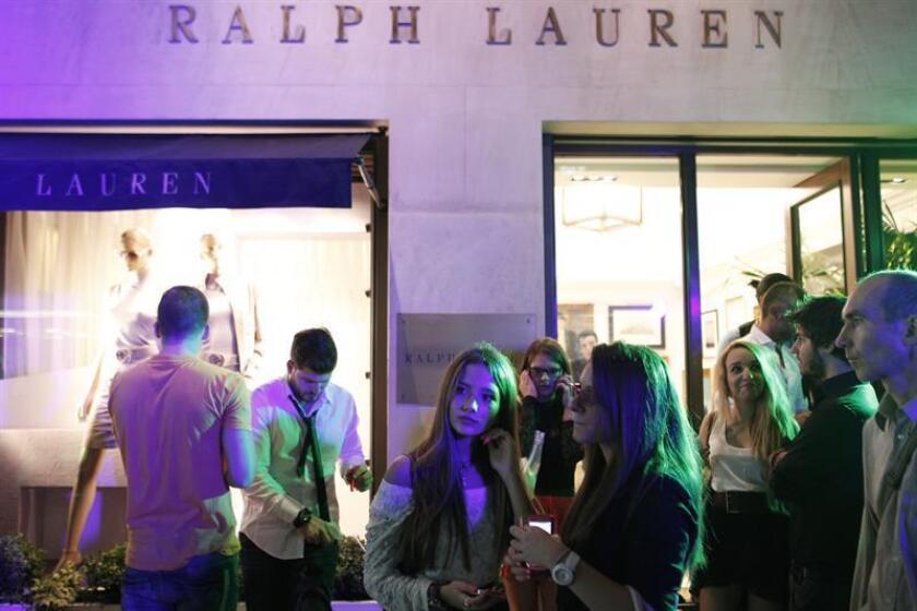 Un grupo de personas camina junto a la vitrina de la tienda Ralph Lauren. EFE/Archivo