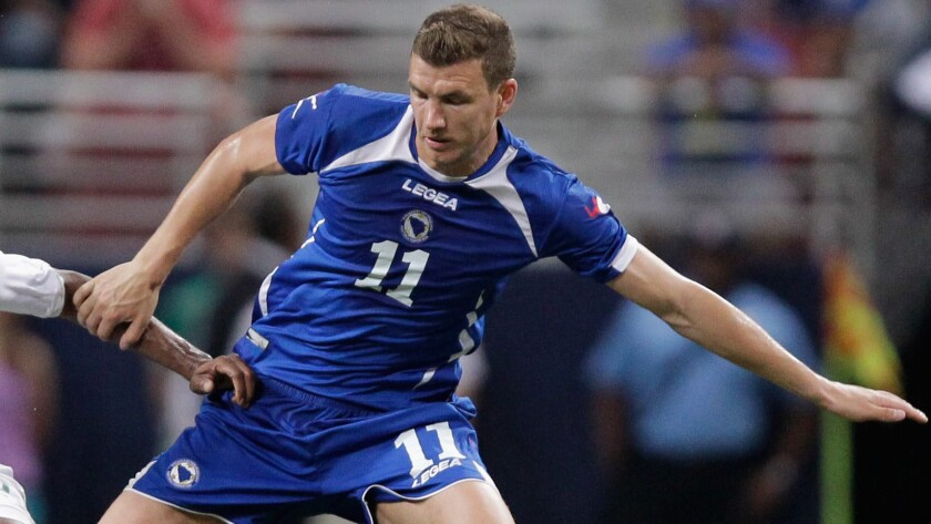Bosnia and Herzegovina's Edin Dzeko battles for the ball during an international friendly match against Ivory Coast on May 30 in St. Louis. Dzeko's experiences as a child during the Bosnian War has made him an advocate for peace and unity in his homeland.