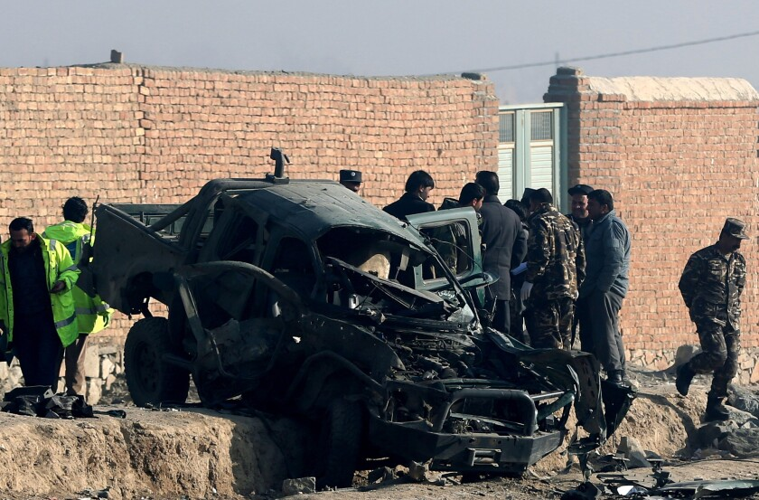 Afghan security forces inspect the site of a suicide attack that killed a police officer in Kabul on Dec. 18.
