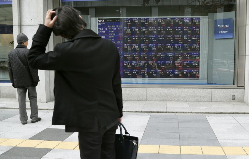 A man scratches his head as he looks at an electronic stock board of a securities firm in Tokyo, Monday, Dec. 9, 2013. Japan has revised its economic growth estimate for the last quarter downward after finding that capital investment slowed more than expected in July-September. The government said Monday that the world's third-largest economy grew an annualized 1.1 percent in the last quarter, less than half the pace of the previous quarter. The previous estimate had put growth at 1.9 percent. (AP Photo/Koji Sasahara)