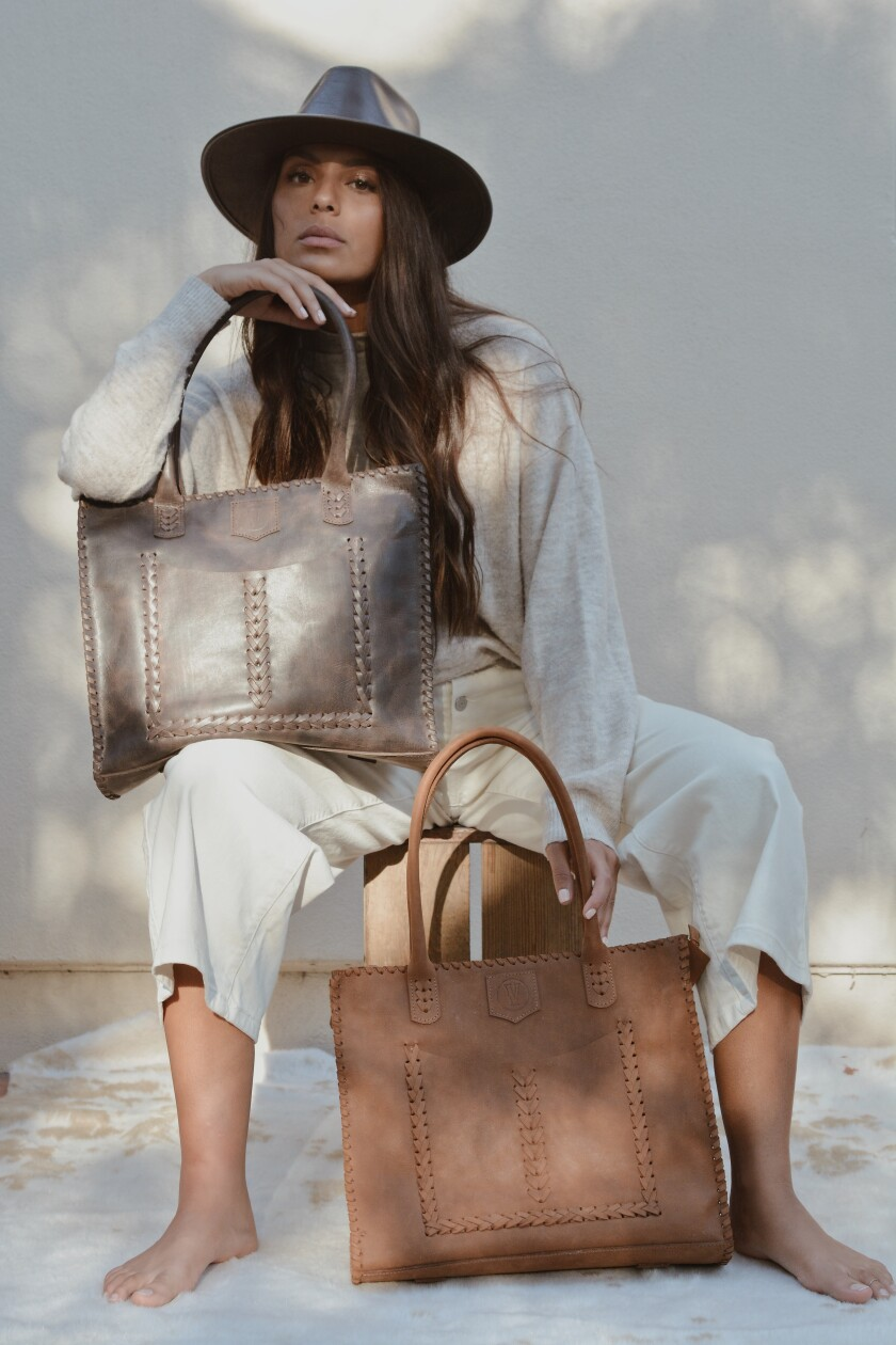 A seated woman holding two large leather bags.