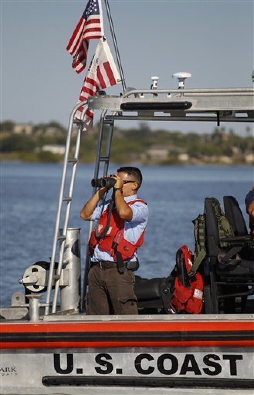 A man on a U.S. Coast Guard uses binoculars on Falcon Lake, a lake that straddles the U.S. Mexico border, where where Coloradan David Hartley is still missing, Thursday, Oct. 7, 2010 in Zapata, Texas. Hartley's wife says her husband was shot to death by Mexican pirates chasing them on speedboats across the lake on Sept. 30 as they returned on Jet Skis from a trip to photograph a historic Mexican church. (AP Photo/Eric Gay)
