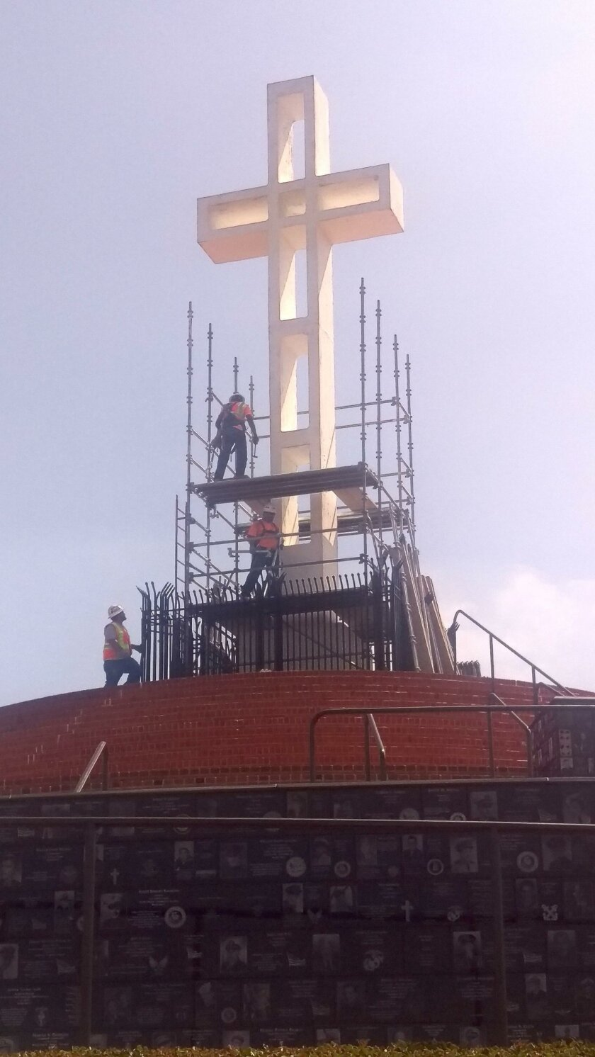 The 27-foot-tall cross is being repaired and repainted by local companies volunteering their expertise.