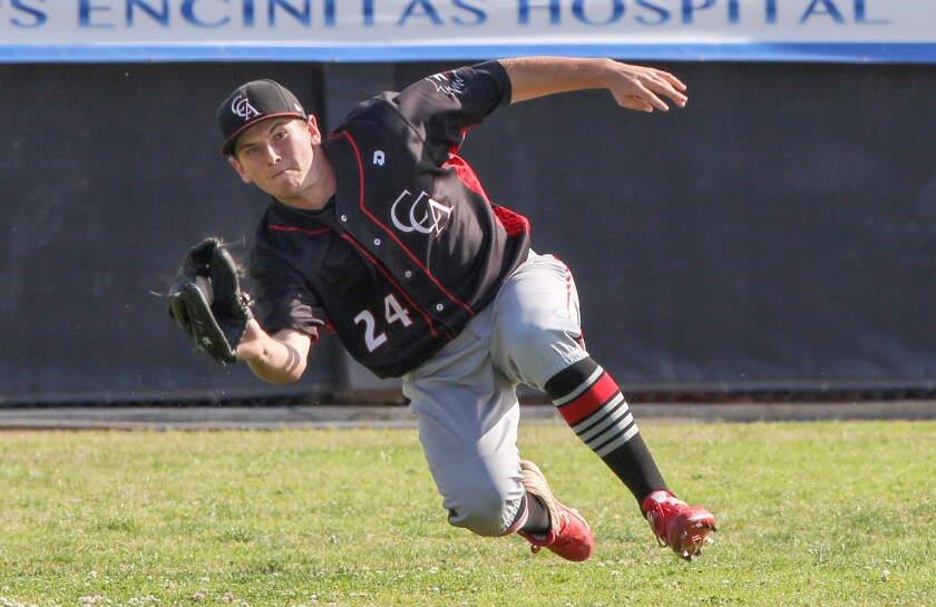 Cole Colleran, of Canyon Crest Academy, falls as he makes a difficult running catch of a fly ball while playing left field. The Carlsbad batter was out.