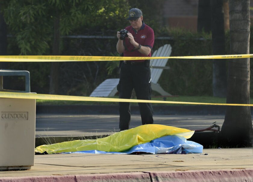 A Los Angeles County sheriff's investigator takes a photo of one of the two men found dead on the grounds of a carwash in Glendora. Police believe they were stabbed.