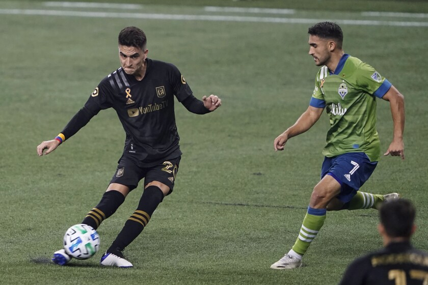 LAFC midfielder Eduard Atuesta tries pass around the defense of Seattle Sounders midfielder Cristian Roldan.
