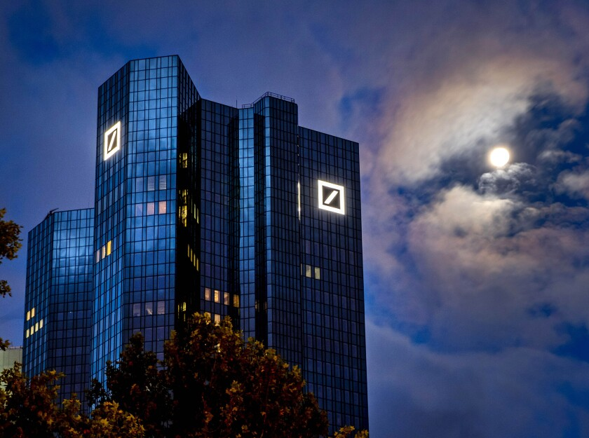 FILE — In this Oct. 4, 2020, file photo, the moon shines next to the headquarters of the Deutsche Bank in Frankfurt, Germany. Deutsche Bank has agreed to pay a fine of more than $100 million to avoid a criminal prosecution on charges it participated in a foreign bribery scheme. Lawyers for the bank waived its right to face an indictment on conspiracy charges Friday, Jan. 8, 2021, during a teleconference with a federal judge in New York City. (AP Photo/Michael Probst, File)