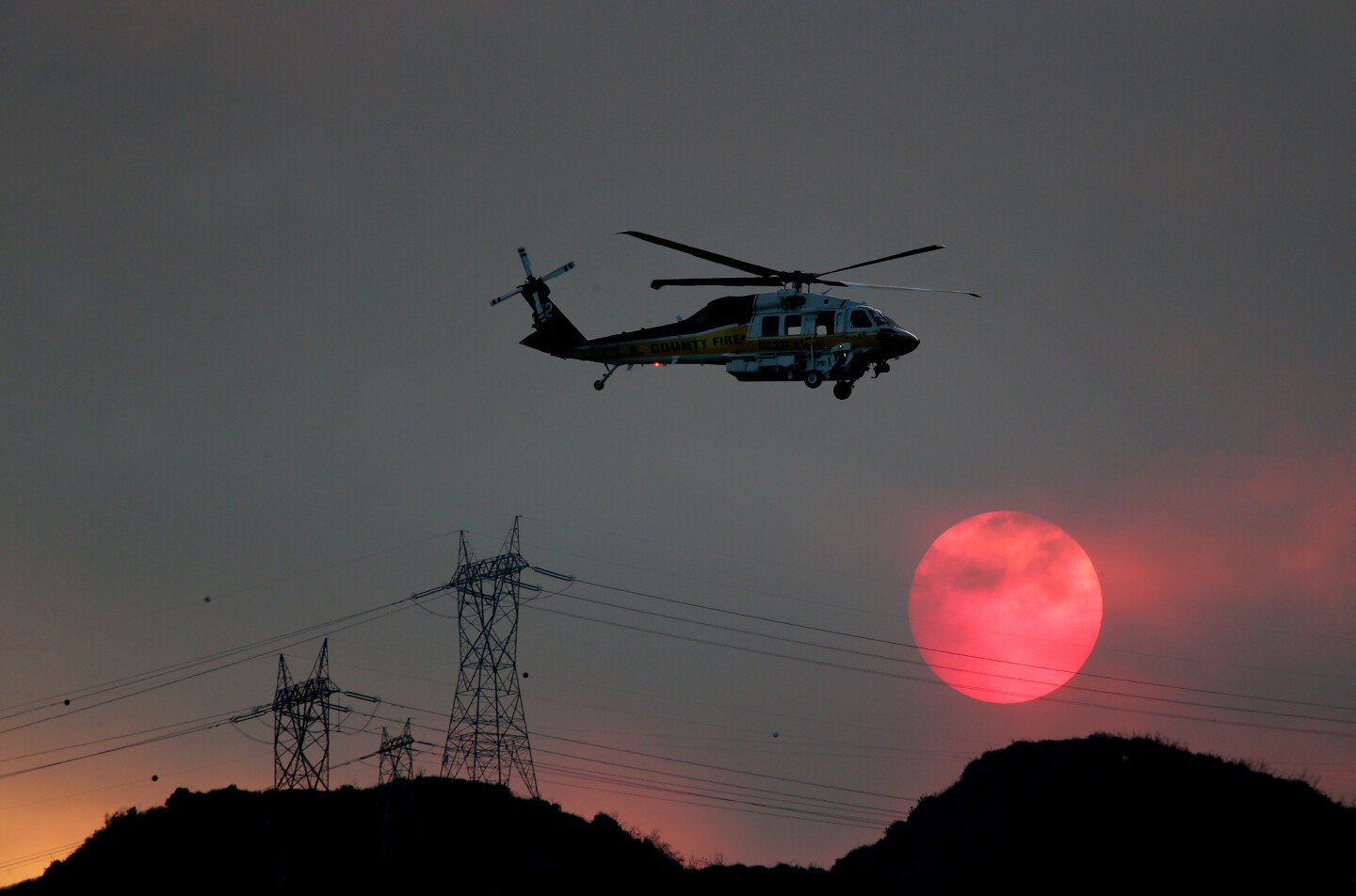 A firefighting helicopter makes an approach to drop water on the Ranch fire