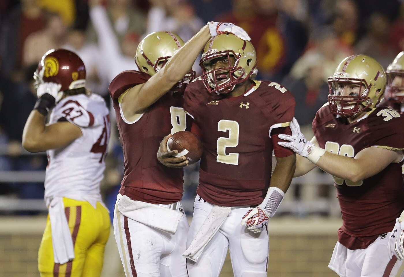 Boston College quarterback Tyler Murphy celebrates with wide receiver Josh Bordner and fullback Bobby Wolford as USC linebacker Scott Felix walks off the field after the Trojans' 37-31 loss to the Eagles on Sept. 13.