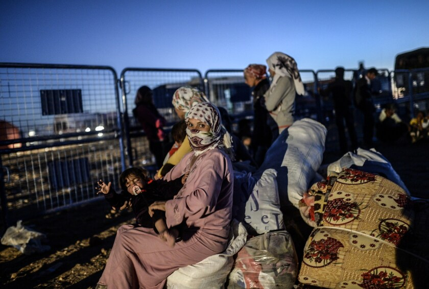 Syrian Kurds wait at a Turkish police checkpoint near the Syrian border town of Suruc on Sept. 21.