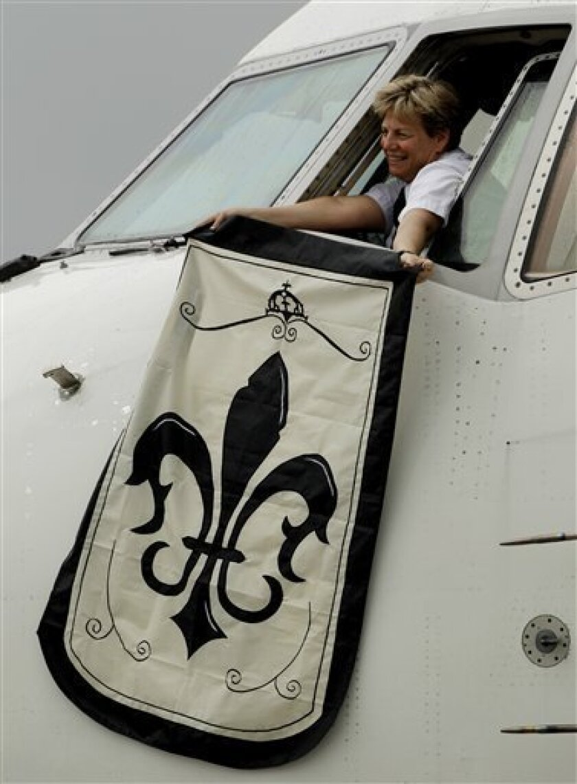 A New Orleans Saints flag is waved out the window of the plane as the team arrives in Miami on Monday, Feb. 1, 2009. The Saints will play the Indianapolis Colts in Super Bowl XLIV Sunday, Feb. 7. (AP Photo/Mark Humphrey)