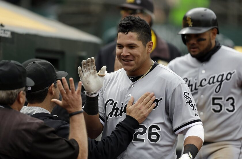 Chicago White Sox's Avisail Garcia (26) is congratulated upon returning to the dugout after hitting a two-run home run off Oakland Athletics' Tyler Clippard in the ninth inning of a baseball game Sunday, May 17, 2015, in Oakland, Calif. White Sox's Melky Cabrera (53) looks on. (AP Photo/Ben Margot)
