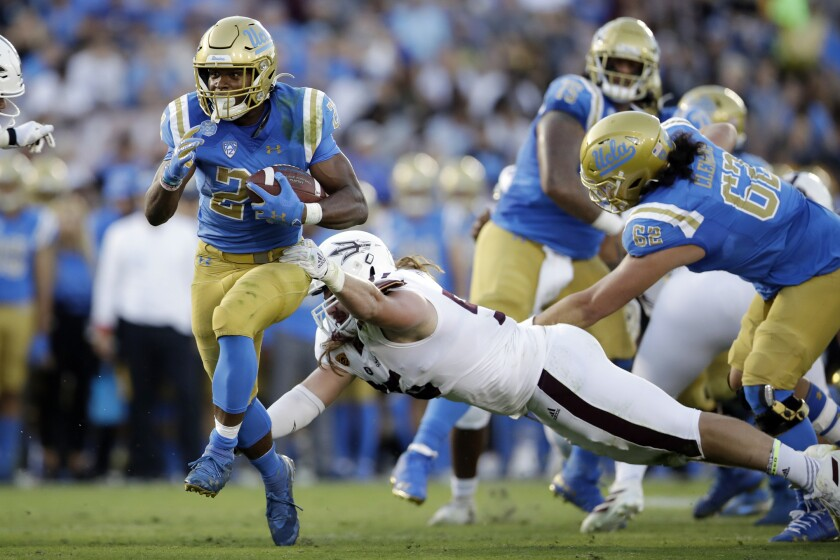 UCLA running back Joshua Kelley, left, runs for a touchdown past Arizona State defensive lineman Roe Wilkins during the first half on Oct. 26 at the Rose Bowl.