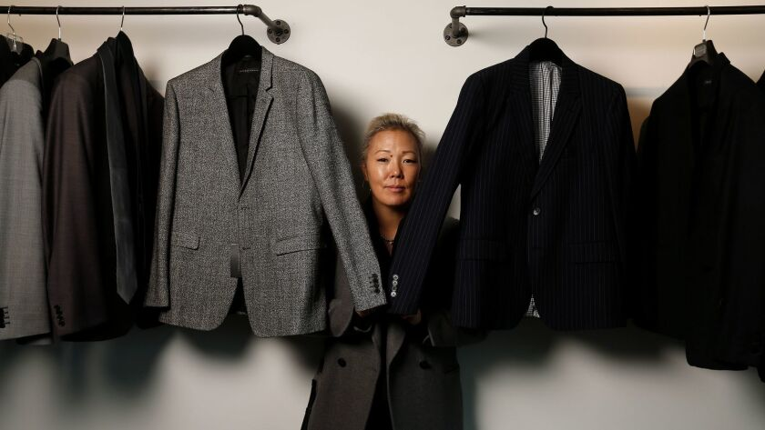 Stylist Jeanne Yang stands with a rack of clothes.