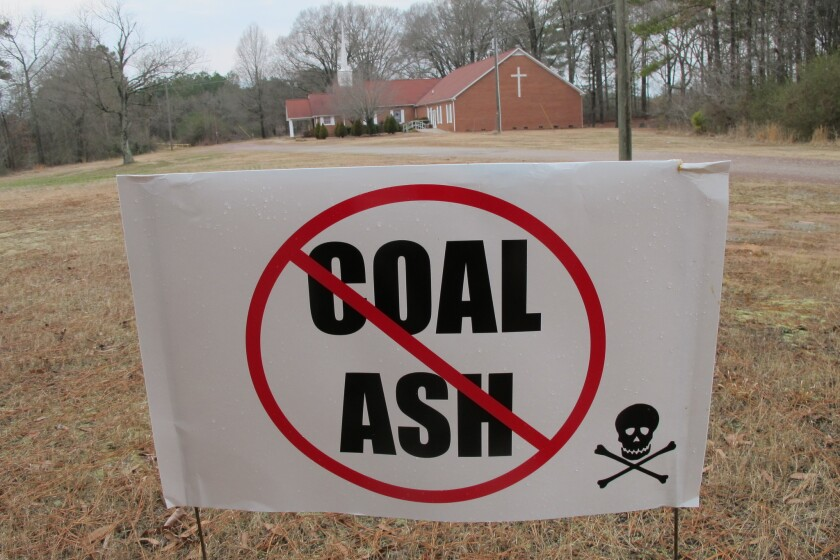 A sign at Mount Calvary Baptist Church in Lee County, N.C., protests a plan by Duke Energy to fill a clay mine pit near the church with eight tons of coal ash from Duke plants more than 100 miles away.