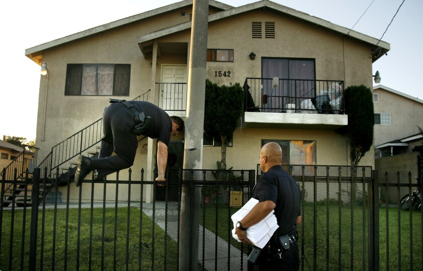 An LAPD officer jumps a fence to let his partner into a housing complex in 2007 while serving notice of a gang injunction. Illegal curfew provisions included in many of the city's gang injunctions were at the center of a federal class-action lawsuit.