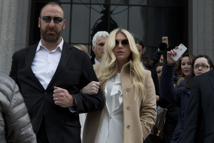 Pop star Kesha, center, leaves court in New York on Friday.