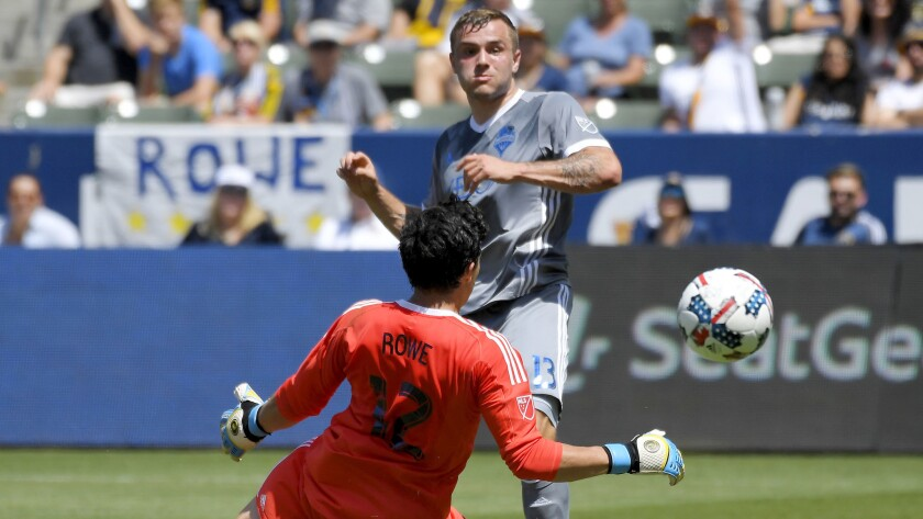 Sounders forward Jordan Morris chips a shot past Galaxy goalkeeper Brian Rowe for a score during the first half Sunday.