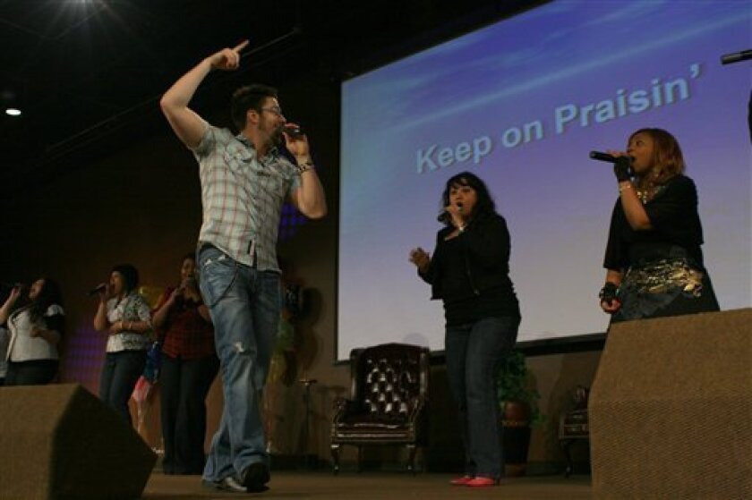 """Danny Gokey, a finalist on the singing competition series """"American Idol,"""" performs at Faith Builders International Ministries in Milwaukee on Friday, May 8, 2009. Gokey volunteered as the song director before trying out for the show. (AP Photo/Carrie Antlfinger)"""