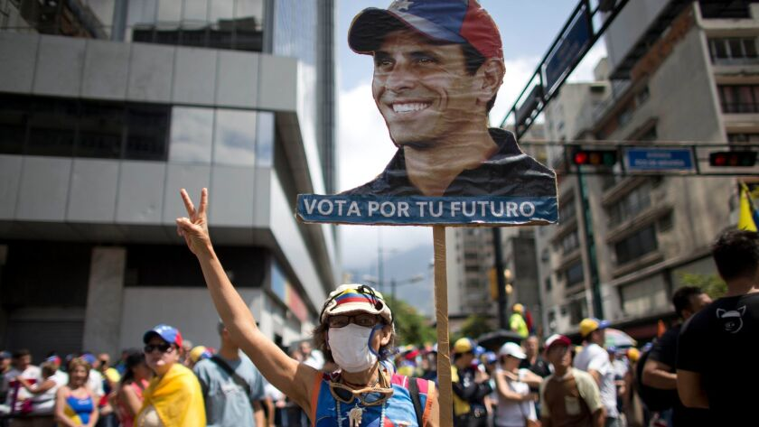 A woman carrying an image of Venezuelan opposition leader Henrique Capriles joins thousands protesting against the government of President Nicolas Maduro on Saturday in Caracas.
