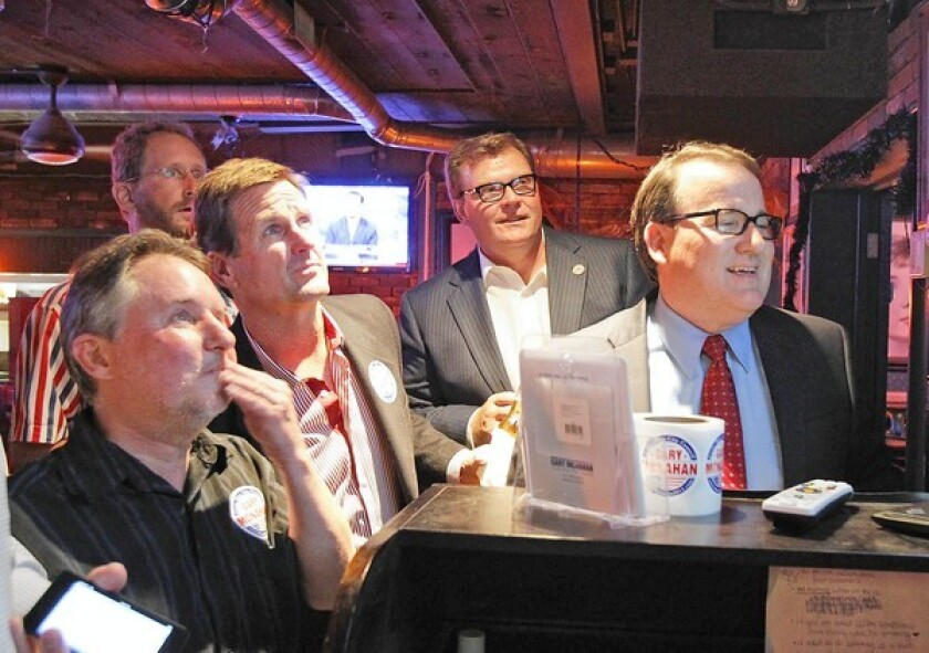 Gary Monahan, far left; Steve Mensinger, second from right and then-Mayor Pro Tem Jim Righeimer, at right, gathered in 2012 to watch early returns in the council race. The three men are among six former Costa Mesa mayors calling for city leaders to reopen parts of the economy, including lifting restrictions on city parks, golf courses and trails.