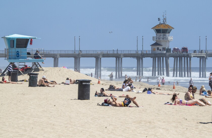 People relax on the sand in Huntington Beach on Monday, despite the state's active-use-only allowance. The city of Huntington Beach is still pursuing a lawsuit against the state to reopen the beach to all forms of activities.