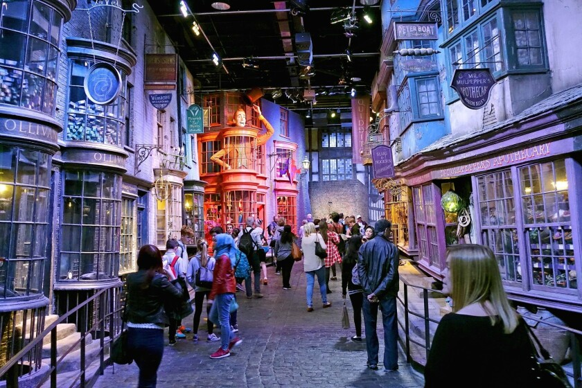 Tourists stroll along the Diagon Alley movie set at The Making of Harry Potter Warner Bros. Studios experience in London.