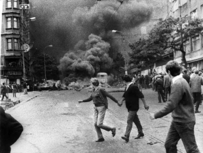 Then: A couple runs from the fire of burning Russian tanks in Prague.