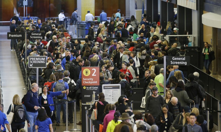 Travelers wait in line for security screening at Seattle-Tacoma International Airport in March.