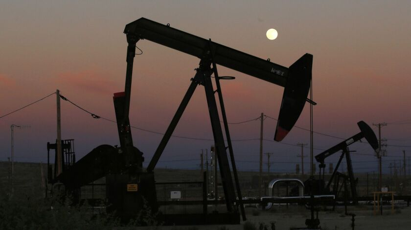 Oil derricks pump as the moon rises in Kern County.