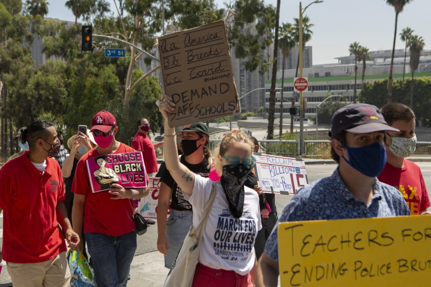 Teachers union members and others march Aug. 3 to demand a safer approach to reopening schools.