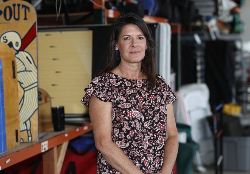 In this Friday, June 5, 2020 photo, Dawn Abbott, chief executive officer of Fun Productions, a small corporate events company that she started in 1991, is shown amid the myriad unused items stacked in the company's northeast Denver warehouse. The woman's events business was hit hard by concellations with the spread of the new coronavirus and now, three months into the downturn, she does not foresee a quick rebound in the future of her enterprise. (AP Photo/David Zalubowski)