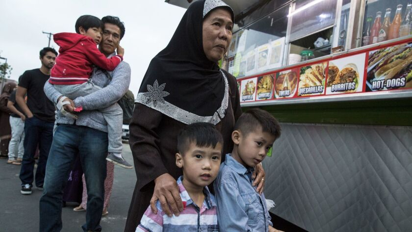 Families wait in line at the taco truck in the parking lot of the Islamic Center of Santa Ana.