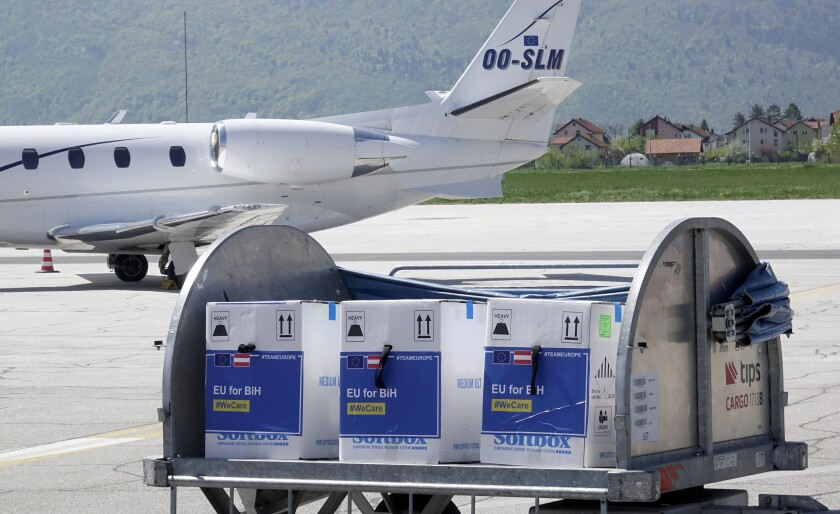 """FILE - In this May 4, 2021, file photo, a container with boxes of the Pfizer vaccine for COVID-19 is delivered at the Sarajevo Airport, Bosnia. The head of the World Trade Organization said Friday, May 7, the U.S. administration's call to remove patent protections on COVID-19 vaccines could help expand fair access to vaccines but might not be the most """"critical issue,"""" as officials in Europe increasingly insisted that more vaccine exports are the more pressing priority. (AP Photo/Eldar Emric, File)"""