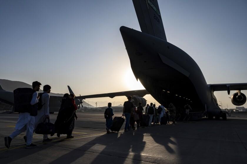 U.S. Air Force airmen guide evacuees board a U.S. Air Force C-17 Globemaster III.