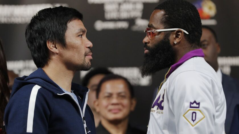Manny Pacquiao, left, and Adrien Broner pose for photographers during a news conference on Wednesday in Las Vegas. The two are scheduled to fight in a welterweight championship bout on Saturday.