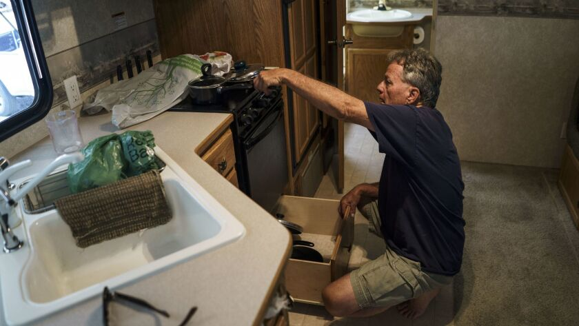 Raymond Taylor packs belongings in his temporary trailer. He and his wife Linda are preparing to mov