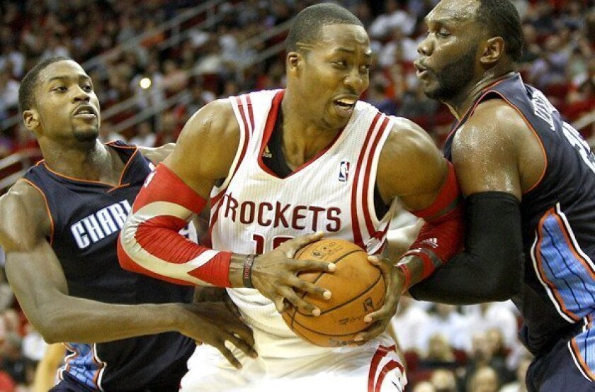 Rockets center Dwight Howard is sure to draw double teams like the one deployed by Charlotte's Michael Kidd-Gilchrist, left, and Al Jefferson.
