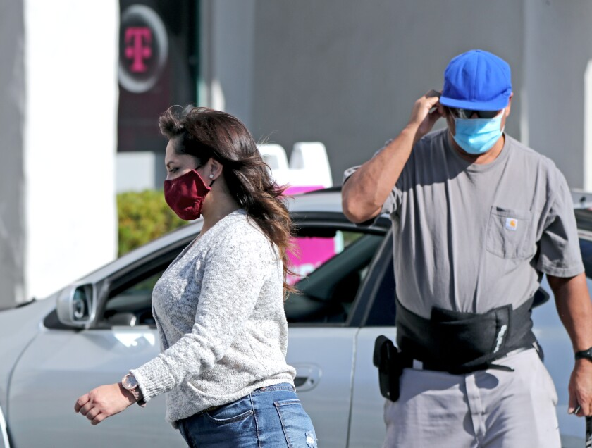 People wear their face masks while outside the 1800 block of Newport Boulevard in Costa Mesa on Saturday, Nov. 14, 2020.