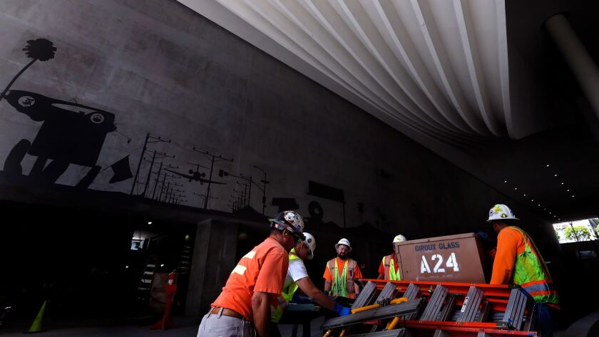 LOS ANGELES, CA-JUNE 1, 2017: Construction workers haul equipment whie working inside the porte coc