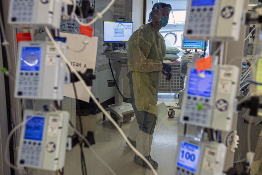 A nurse in full protective gear is seen through a glass door, framed by electronic medical instruments on poles