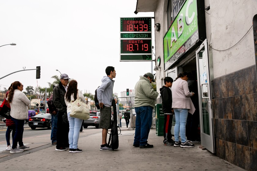 Signs indicate the price of the dollar against the peso at a money exchange near the San Ysidro Port of Entry on Friday.