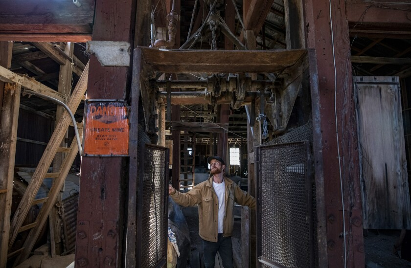 Brett Underwood stands between massive wooden posts of the headframe of the Union Mine in Cerro Gordo ghost town.