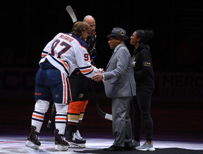 Connor McDavid of the Edmonton Oilers shakes hands with Willie O'Ree along with Blake Bolden and Ryan Getzlaf of the Ducks before the game in celebration of Black History Month at Honda Center on Wednesday.