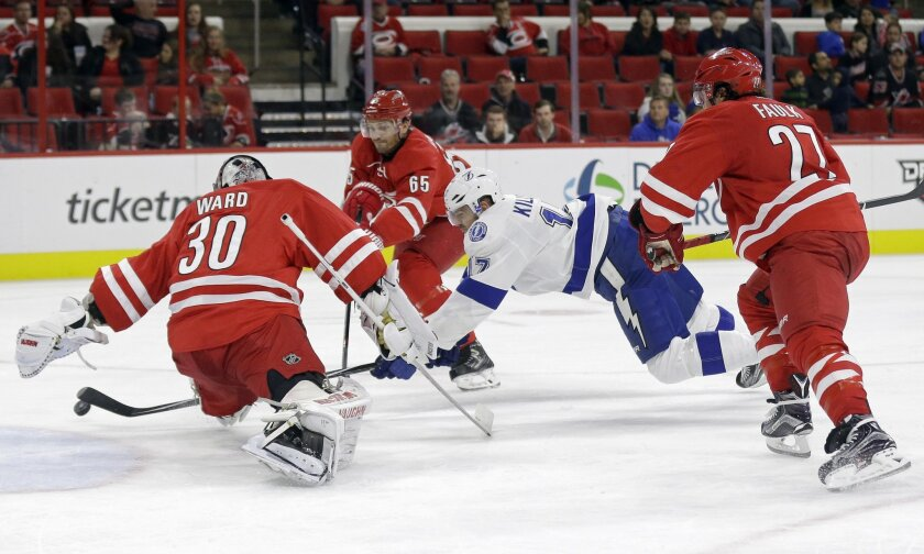 Carolina Hurricanes goalie Cam Ward (30), Ron Hainsey (65) and Justin Faulk (27) defend against Tampa Bay Lightning's Alex Killorn (17) during the second period of an NHL hockey game in Raleigh, N.C., Sunday, Nov. 1, 2015. (AP Photo/Gerry Broome)