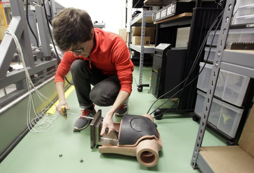 In this March 17, 2016 photo, Elizabeth McCalley prepares a dummy for testing the impact of a ball to a person's chest at the National Operating Committee on Standards for Athletic Equipment facility in Rockford, Tenn. The NOCSAE sets safety standards for sports gear. A blow to the chest _ one that